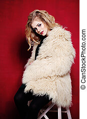 Fashion Woman with Curly Blond Hair wearing White Fur Coat