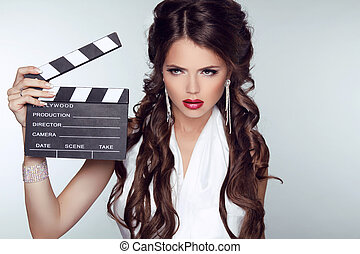 Fashion woman with sexy red lips holding cinema clap. Super...