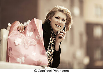 Fashion woman with shopping bags calling on the phone