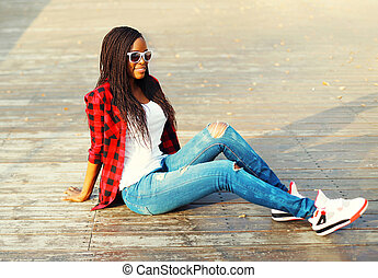 Fashion young african woman sitting in a city park, wearing a red checkered shirt and sunglasses