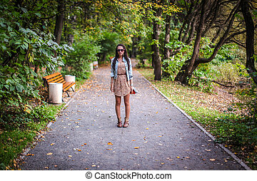 Fashion young beautiful girl walks in the park on a sunny autumn day