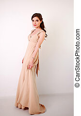 Fashion young brunette woman in pastel long dress in studio on white background