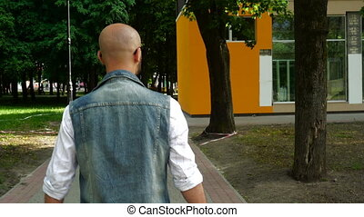 Fashion young man in denim clothes walks down the street...