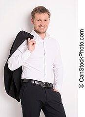 Fashion young man in white shirt. guy holds black jacket over wall