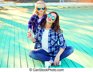 Fashion young mother with child daughter wearing a sunglasses and checkered shirt sitting in the city