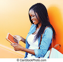 Fashion young smiling african woman using tablet pc in the city over colorful orange background