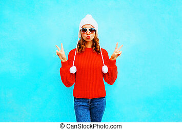 Fashion young woman in a knitted hat and sweater on blue background