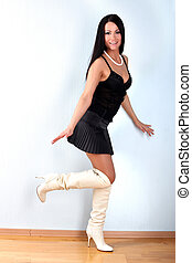 fashion young woman in black outfit and white boots in room