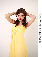 Fashion young woman in long yellow dress, studio on white