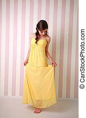Fashion young woman in long yellow dress, studio