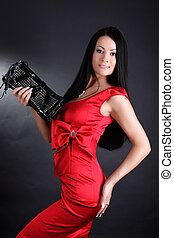 fashion young woman in red dress with clutch bag