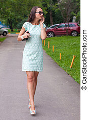 Fashion young woman talking on the phone and walking