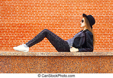Fashion young woman wearing a black rock style lying over...