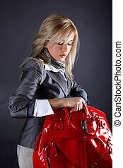 fashion young woman with red bag looking inside