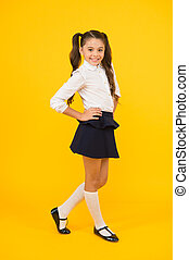 Fashionable and classy. Small girl with long hair smiling in fashionable school uniform. Happy schoolchild with fashionable look on yellow background. Fashionable back to school trends