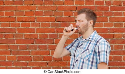 Fashionable and stylish guy with a beard smoking a vape...
