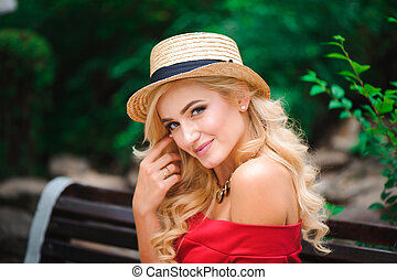 Fashionable attractive blonde woman in red dress sitting on chair