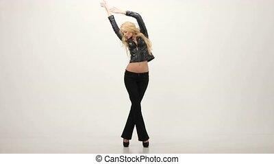 Fashionable beautiful blonde woman posing in studio in black dress. Sexy look.