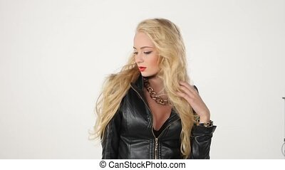 Fashionable beautiful blonde woman posing in studio in black dress. Sexy look. Slow motion.