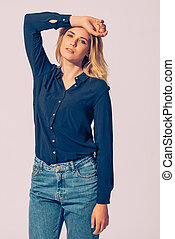 Fashionable beauty. Studio shot of beautiful young woman wearing black shirt holding hand over head and looking at camera