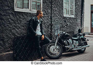 Fashionable biker dressed in a black leather jacket and jeans leaning on a wall near his retro motorcycle on old Europe street.
