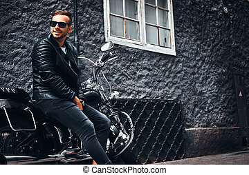 Fashionable biker dressed in a black leather jacket and jeans sitting on his retro motorcycle on an old Europe street.