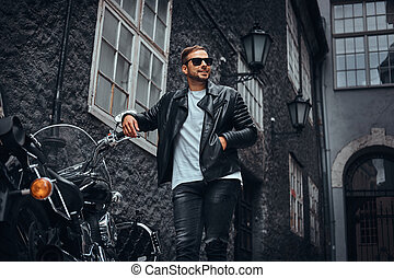Fashionable biker in sunglasses dressed in a black leather jacket and jeans leaning on his retro motorcycle on an old Europe street.