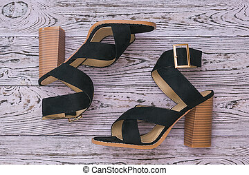 Fashionable black women's summer shoes on a wooden background. Flat lay.