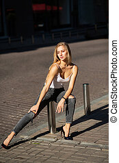 Fashionable blonde girl with long hair wearing jeans and t shirt posing at the city in sun rays