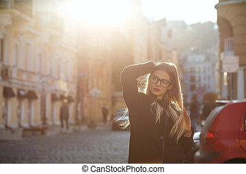 Fashionable blonde model with long hair wearing coat, posing in sun glare. Empty space