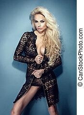 Fashionable blonde sexy woman wearing black dress posing.