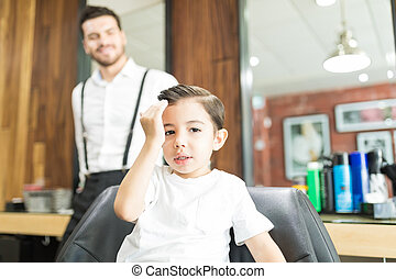 Fashionable Boy Touching Hair After Haircut In Barber Shop