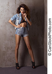 Fashionable brunette beautiful woman posing in studio wearing short and jacket jeans, looking at camera.