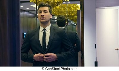 Fashionable businessman standing in front of the mirror