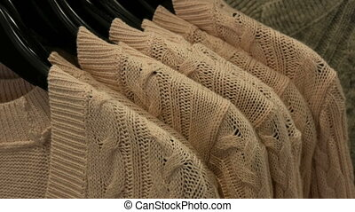 Fashionable collection of warm clothes. Large number of new warm stylish sweaters of different colors hanging on hangers in the clothing store shopping center or mall.