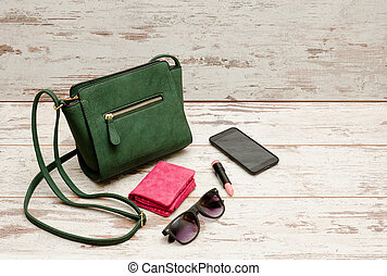 Fashionable concept: eyeshadows, handbag, glasses, lipstick, wallet on a wooden background. top view