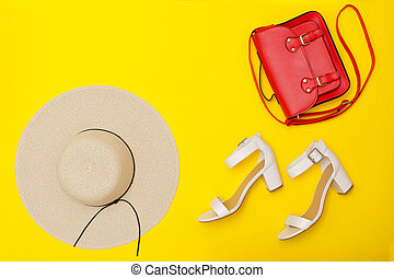 Fashionable concept. Women's beach hat, red handbag, white shoes. Yellow background, top view