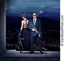 Fashionable couple with automatics - Fashionable couple -...