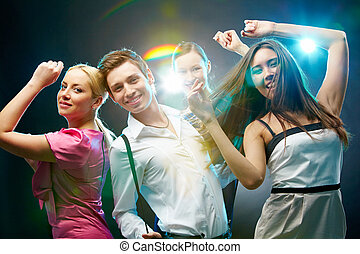 Fashionable dancers - A group of four friends dancing and...