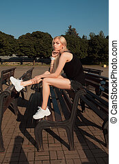 Fashionable dressed young model in stylish apparel posing on a bench in sunny day