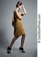 Fashionable emotional woman in modern yellow dress