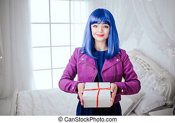 Fashionable freak. Portrait of glamour smiling beautiful woman with blue hair is holding gift in the white bedroom. Fashion and beauty concept