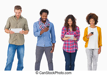Fashionable friends standing in a row using media devices