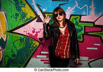 Fashionable girl and colorful graffiti wall
