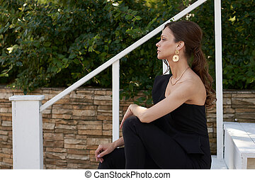 Fashionable girl in a black dress and golden earrings in the city