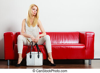 Fashionable girl with bag handbag on red couch