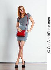 Fashionable girl with red bag handbag.