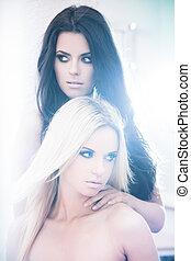 Fashionable girls - Two beautiful women posing in bleached...