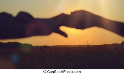 Fashionable happy couple  join hands runs across the field and hug in sunset light, lifestyle - happiness