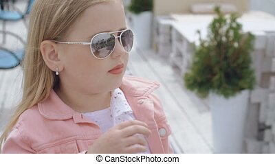 Fashionable little blonde puts off sunglasses and looks at...